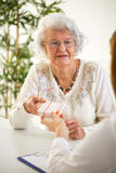 Doctor giving pills to beutiful senior woman Stock Images