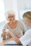 Doctor giving pills to elderly woman in medical office Royalty Free Stock Photos