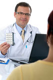Doctor giving pills to a patient Stock Photos