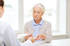 Doctor giving prescription and drug to woman Stock Photos