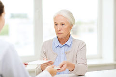 Doctor giving prescription and drug to woman Stock Photo