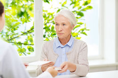 Doctor giving prescription and drug to woman Royalty Free Stock Photo