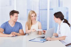 Doctor giving prescription paper to couple in clinic Royalty Free Stock Photos