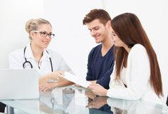 Doctor giving prescription paper to couple Royalty Free Stock Image
