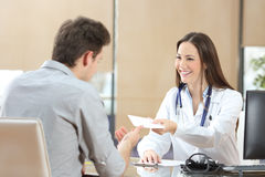 Doctor giving a prescription to her patient Stock Photography