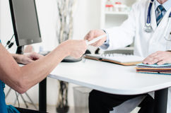 Doctor giving a prescription to his patient Royalty Free Stock Image