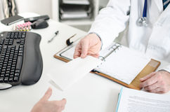 Doctor giving a prescription to his patient Stock Image