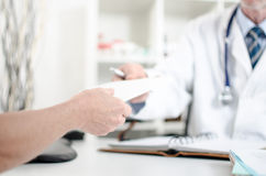 Doctor giving a prescription to his patient Stock Images