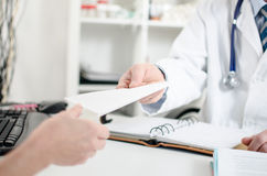 Doctor giving a prescription to his patient Royalty Free Stock Photos