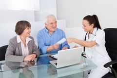 Doctor Giving Prescription To Senior Couple In Clinic Royalty Free Stock Photography