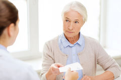 Doctor giving prescription to senior woman Royalty Free Stock Photography