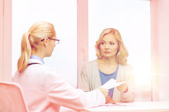 Doctor giving prescription to woman at hospital Royalty Free Stock Photos