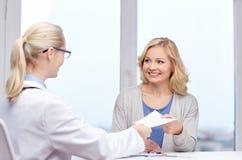 Doctor giving prescription to woman at hospital Stock Photos