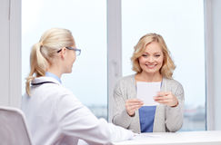 Doctor giving prescription to woman at hospital Stock Photos