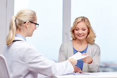 Doctor giving prescription to woman at hospital Stock Photography