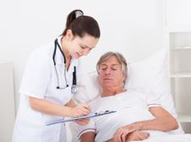 Doctor giving prescriptions. Senior Male Patient Looking At Doctor Writing On Clipboard Royalty Free Stock Image