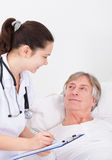 Doctor Giving Prescriptions. Senior Male Patient Looking At Doctor Writing On Clipboard Stock Photography