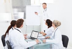 Doctor giving presentation to colleagues Stock Images