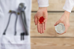 Doctor giving red pills and glass of water, hands close up with desktop on background, top view.  Stock Image