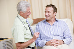 Doctor giving smiling man checkup Royalty Free Stock Photography