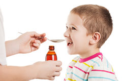 Doctor giving spoon of syrup to boy Royalty Free Stock Photography