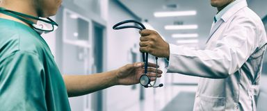 Doctor giving stethoscope to surgeon Referral. Doctor passing stethoscope to surgeon. Concept of specialist referral patients from general practitioner GP for royalty free stock image