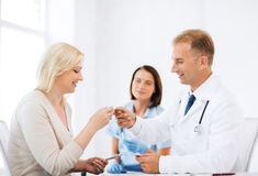 Doctor giving tablets to patient in hospital Stock Image