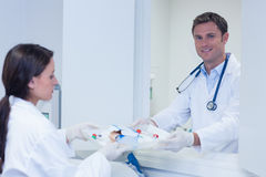 Doctor giving tray with blood sample to his colleague Royalty Free Stock Photos