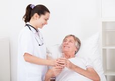 Doctor giving water to patient Royalty Free Stock Photo