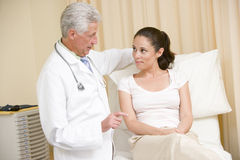 Doctor giving woman checkup in exam room Royalty Free Stock Photo