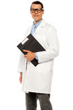 Doctor in glasses carrying clipboard Royalty Free Stock Photo