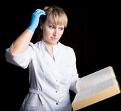 Doctor in gown and rubber gloves reading a medical book to confirm that his patient is in excellent health.  Royalty Free Stock Photo