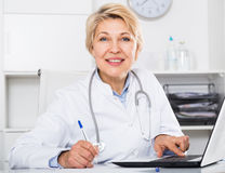 Doctor in gown waiting for patient Stock Photography
