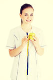 Doctor with a green apple and measuring tape. Royalty Free Stock Image
