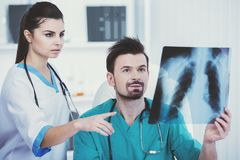 Doctor in green medical gown holds roentgen. Medical staff looks at roentgen. Serious doctors Stock Images