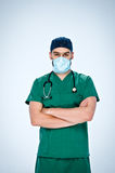 The doctor in green scrubs,blue  mask and blue cap folded his arms across his chest. The doctor in green scrubs,blue mask and blue cap folded his arms across Royalty Free Stock Images