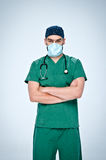 The doctor in green scrubs, mask and cap folded his arms across his chest. Around his neck hangs a black doctor pediatric stethoscope Royalty Free Stock Photo