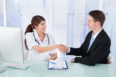 Doctor greeting businessman in clinic Royalty Free Stock Photo