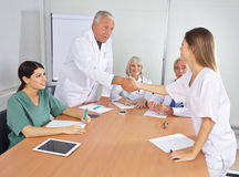 Doctor greeting new colleague in team Stock Images