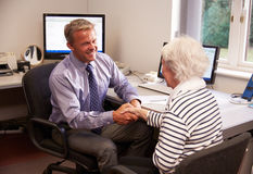 Doctor Greeting Senior Female Patient With Handshake Royalty Free Stock Photo