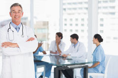 Doctor with group around table in background at hospital Stock Photos