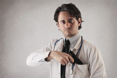 Doctor with a gun coming out of his pocket royalty free stock photo