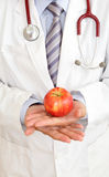 Doctor hand with a apple. Doctor's hand with a apple for health concept Stock Photography