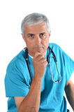 Doctor With Hand on Chin. Serious middle aged doctor with his hand on his chin, Man is wearing scrubs with a stethoscope around his neck. Vertical Format over Stock Photo