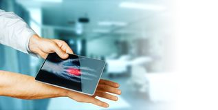 Doctor Hand With Digital Tablet Scans Patient Hand, Medicine Technology Concept royalty free stock photography