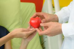 Doctor hand giving red heart to patient woman Stock Images