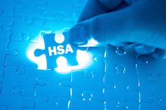Free Doctor Hand Holding A Jigsaw Puzzle With HSA Health Savings Acc Stock Photos - 129145593