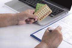 Doctor hand holding birth control pills Stock Photo