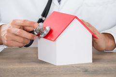 Doctor Hand Holding Stethoscope On House Model Stock Photography