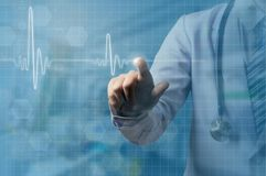 Doctor hand and index finger touching on screen of ECG wave royalty free stock image